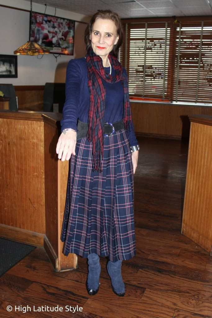 style book author in pleated plaid midi, boots, sweater and tartan scarf