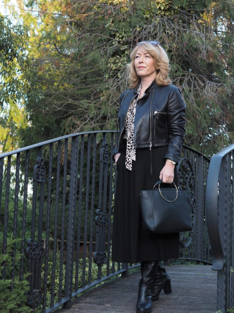 Laurie of Vanity and me in black leather jacket, boots, skirt, bag with black and with bow print shirt