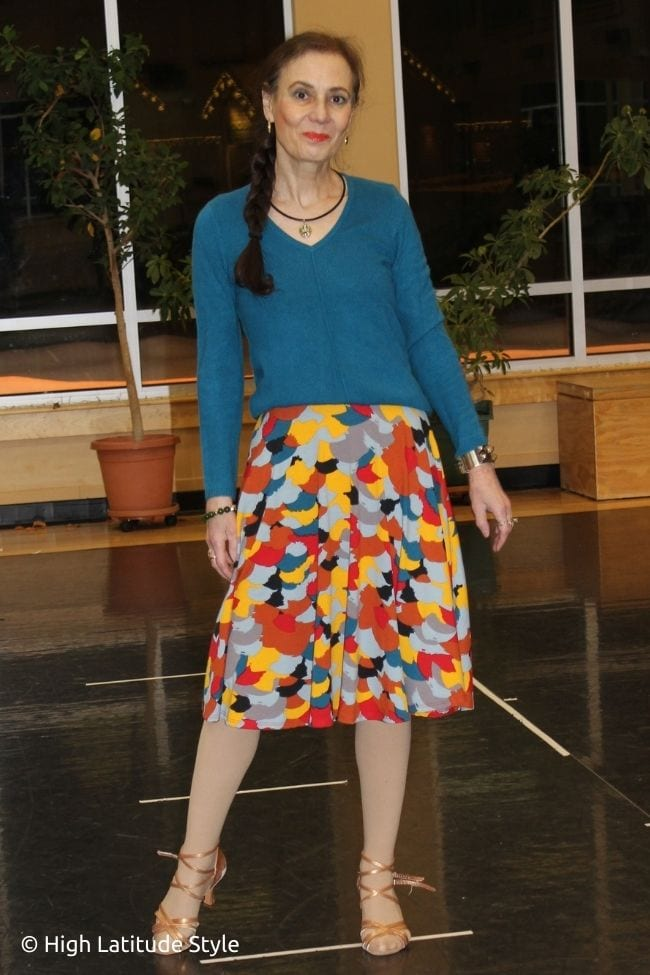 influencer in colorful fun skirt, teal v-neck sweater
