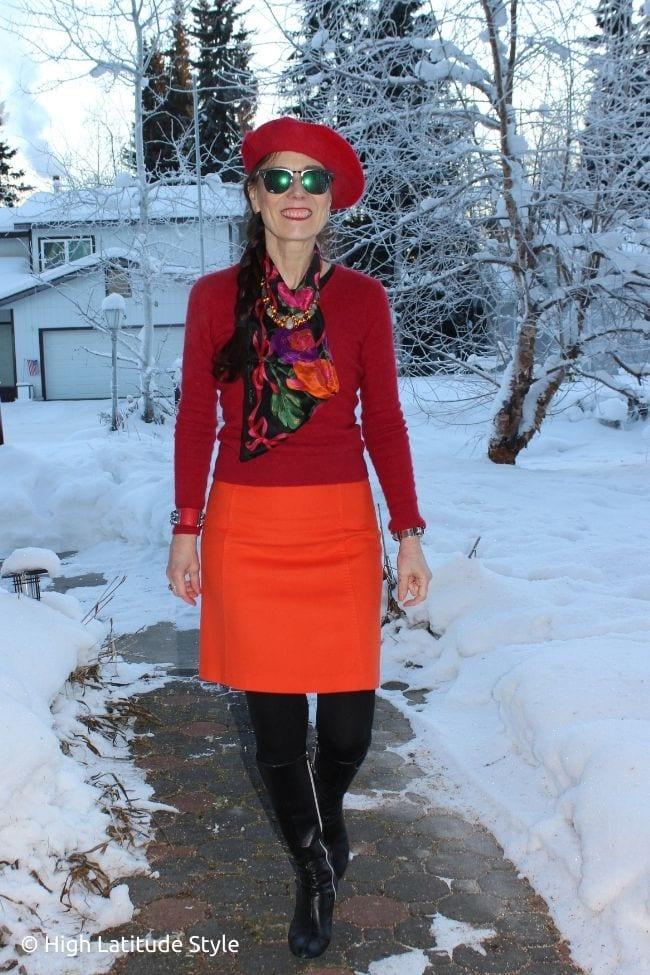 influencer in orange skirt, red sweater and head topper, black scarf, boots and tights