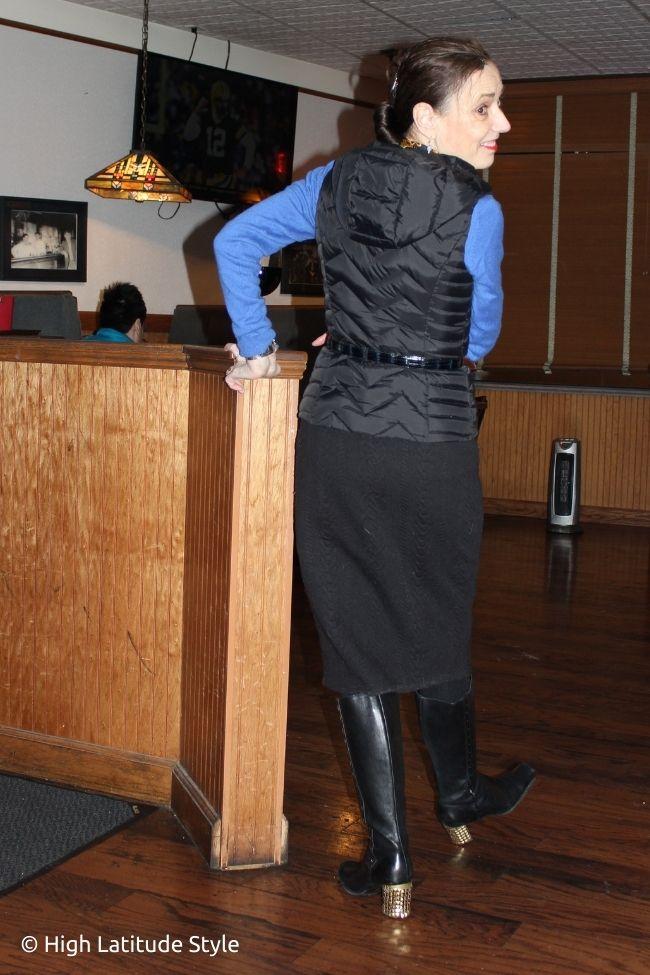 influencer in blue top, black vest, boots skirt