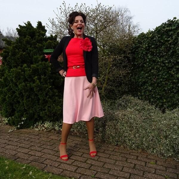 Nancy in pink skirt red top black jacket red sandals