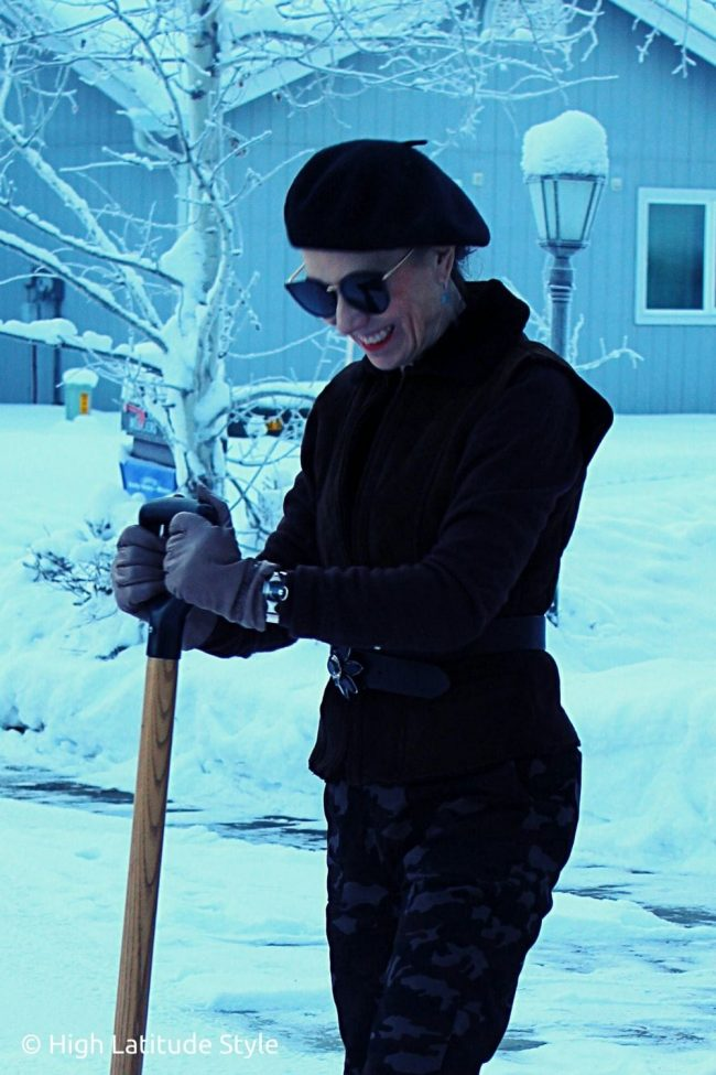 Alaskan influencer with iconic SUNGAIT sun protection glasses removing ice from a driveway