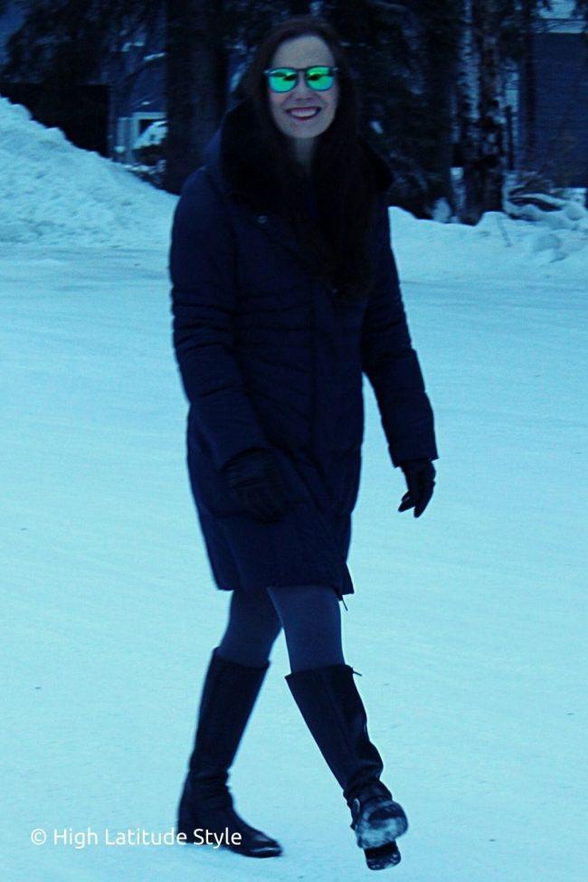 stylist wearing SUNGAIT mirrored eyewear, downcoat, riding boots, tights