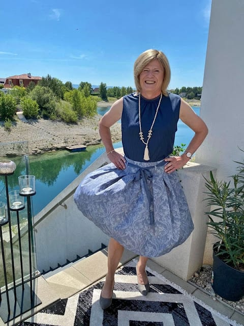 Nadine in Dirndl skirt and blue top in the sunshine on a deck