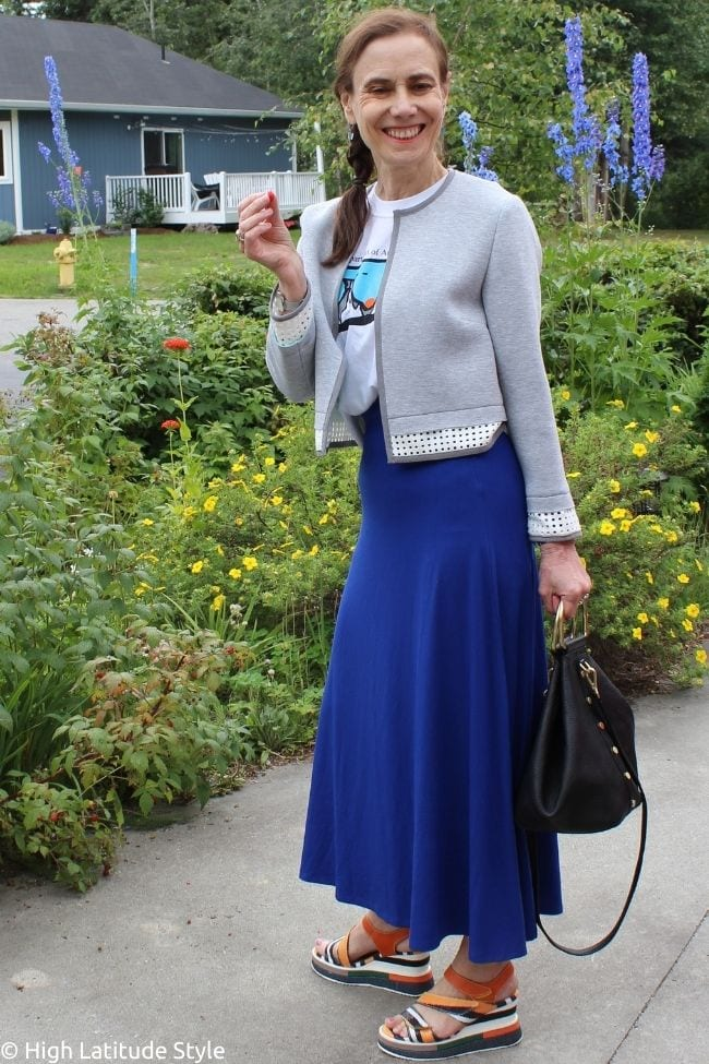 stylist in Coolibar sunprotective bell skirt with gray jacket and graphic T-shirt, sandals
