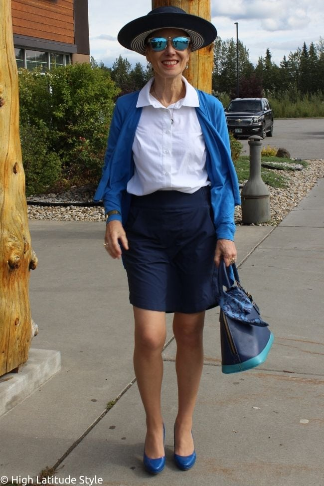business casual sun safe outfit idea with button down shirt, skorts, sunglasses, cardigan