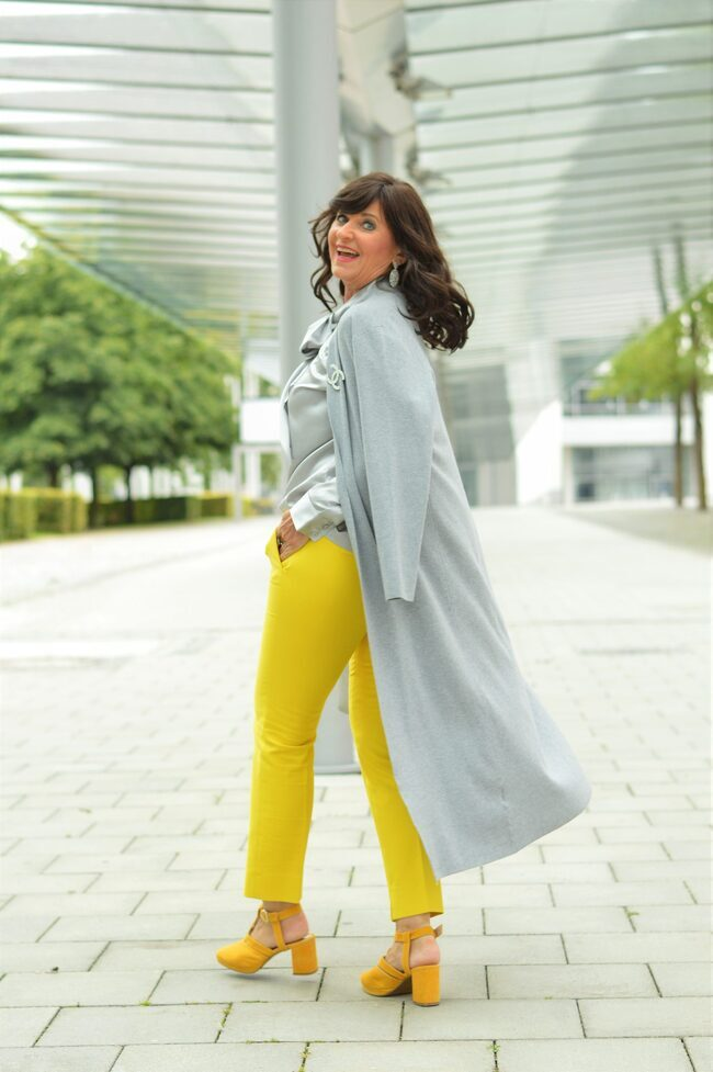Martina Berg in yellow pants and sandals, gray top and coat