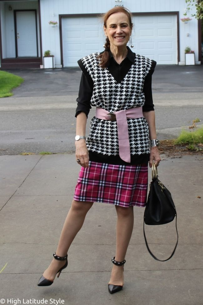 casual Friday outfit idea with button down shirt, hounds tooth vest, plaid skirt, belt