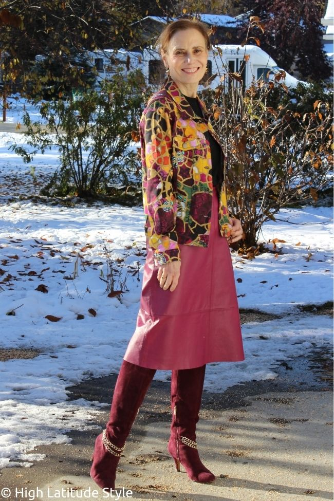 pink skirt with burgundy tall boots black top and colorful jacket