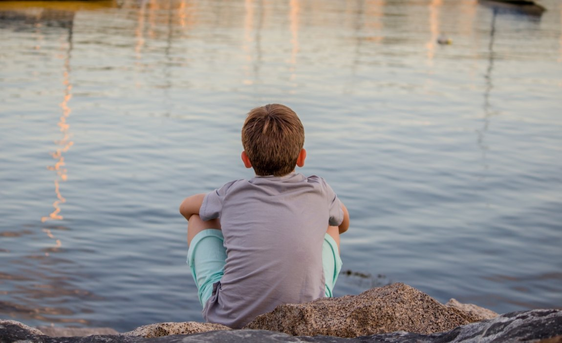 a highly sensitive boy sits by a lake