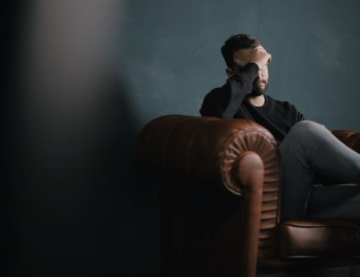 "A highly sensitive man, seated, looking tired and dealing with overstimulation and intense emotions, as described in the book ""The Highly Sensitive Man"" by Tom Falkenstein."