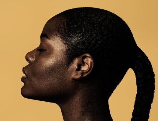 A strong, powerful Black woman in profile against a yellow background, with a sensitive expression on her face.