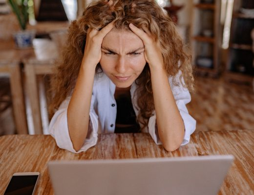 A woman experiencing a flood of frustration, stress and worry while working at her computer in her home office