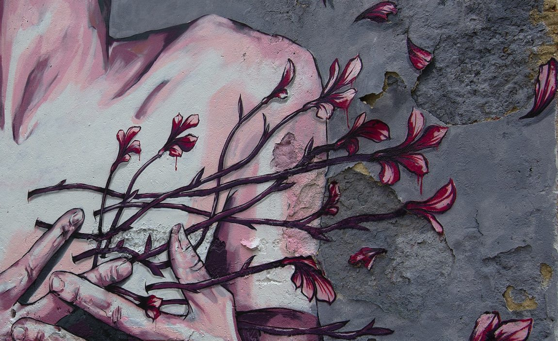 Wind blows away the petals of flowers held by a sensitive woman bravely facing a crisis