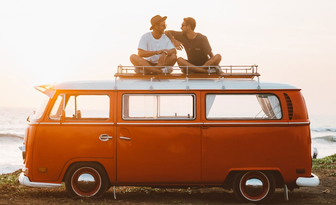Two highly sensitive people relaxing on top of their camper van and enjoying a fun afternoon on a road trip.