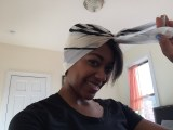Square, tan headscarf tied in a double knot so that the front point is secured by the two longer pieces.