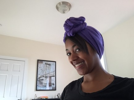 Long, rectangular, purple scarf tied around head and twisted to form a large knot.