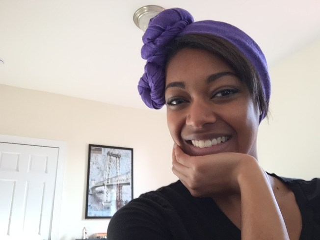 Long, rectangular, purple scarf tied around head with two loose ends each individually coiled into two side by side knots.
