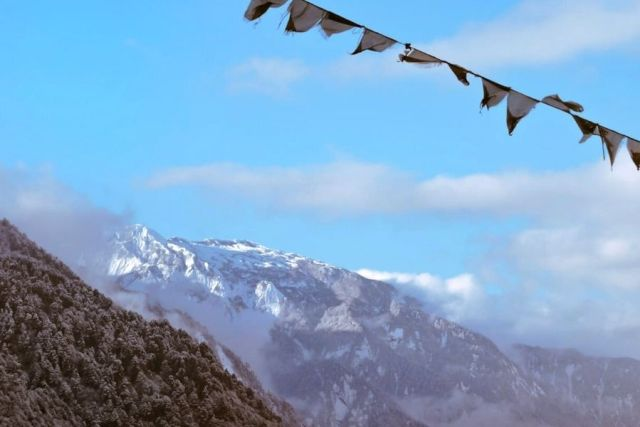 Prayer flags fluttering against the backdrop of the snow capped peaks in North Sikkim