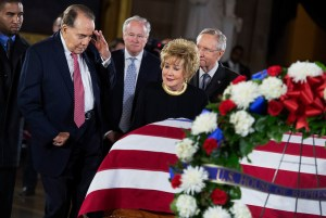 """UNITED STATES - DECEMBER 20:  Former Sen. Bob Dole, R-Kan., salutes the casket of the late Sen. Daniel Inouye, D-Hawaii, as his body lies in state in the Capitol rotunda, as Dole's wife, former Sen. Elizabeth Dole, R-N.C., looks on.  Bob Dole and Inouye knew each other since they were recovering from World War II battle wounds.  Dole was assisted to the casket saying """"I wouldn't want Danny to see me in a wheelchair.""""  (Photo By Tom Williams/CQ Roll Call)"""