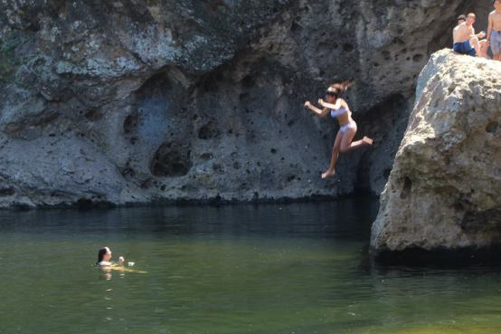 My first jump off the 10-foot cliff as my best friend cheers me on from the water
