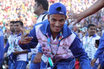 An athlete from team India throws up the deuces as he makes his way from the entrance tunnel to the Coliseum field during the Special Olympics World Games Opening Ceremony on Saturday.