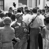 Aug. 15, 1965: Local residents and newsmen converge on California Gov. Pat Brown, arrow, as he arrives at Jacob Riis High in Watts Riot area to have lunch with high-ranking National Guard officers. This photo was published in the Aug. 16, 1965 Los Angeles Times.