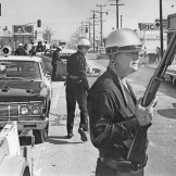 Los Angeles police officers stand guard as debris of day of violence is cleared from the intersection of Avalon Blvd. and Imperial Hwy., one of the worst trouble spots from which violence was spreading. Staff file photo from 1965 Watts Riots.