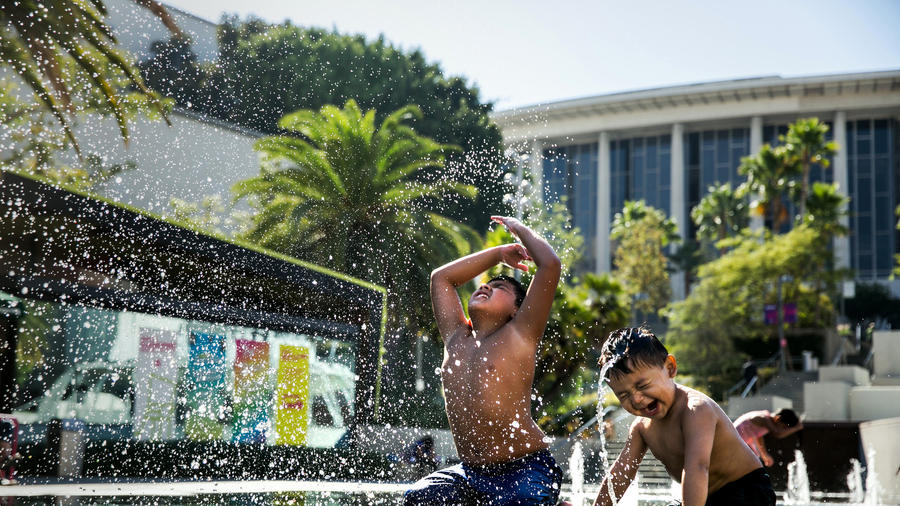 Nathan Gomez, 2, right, learns to mimic his older brother, Matthew Gomez, 9, left, as they use their heads to fling water in the air while playing at the water fountain at Grand Park. (Marcus Yam / Los Angeles Times)