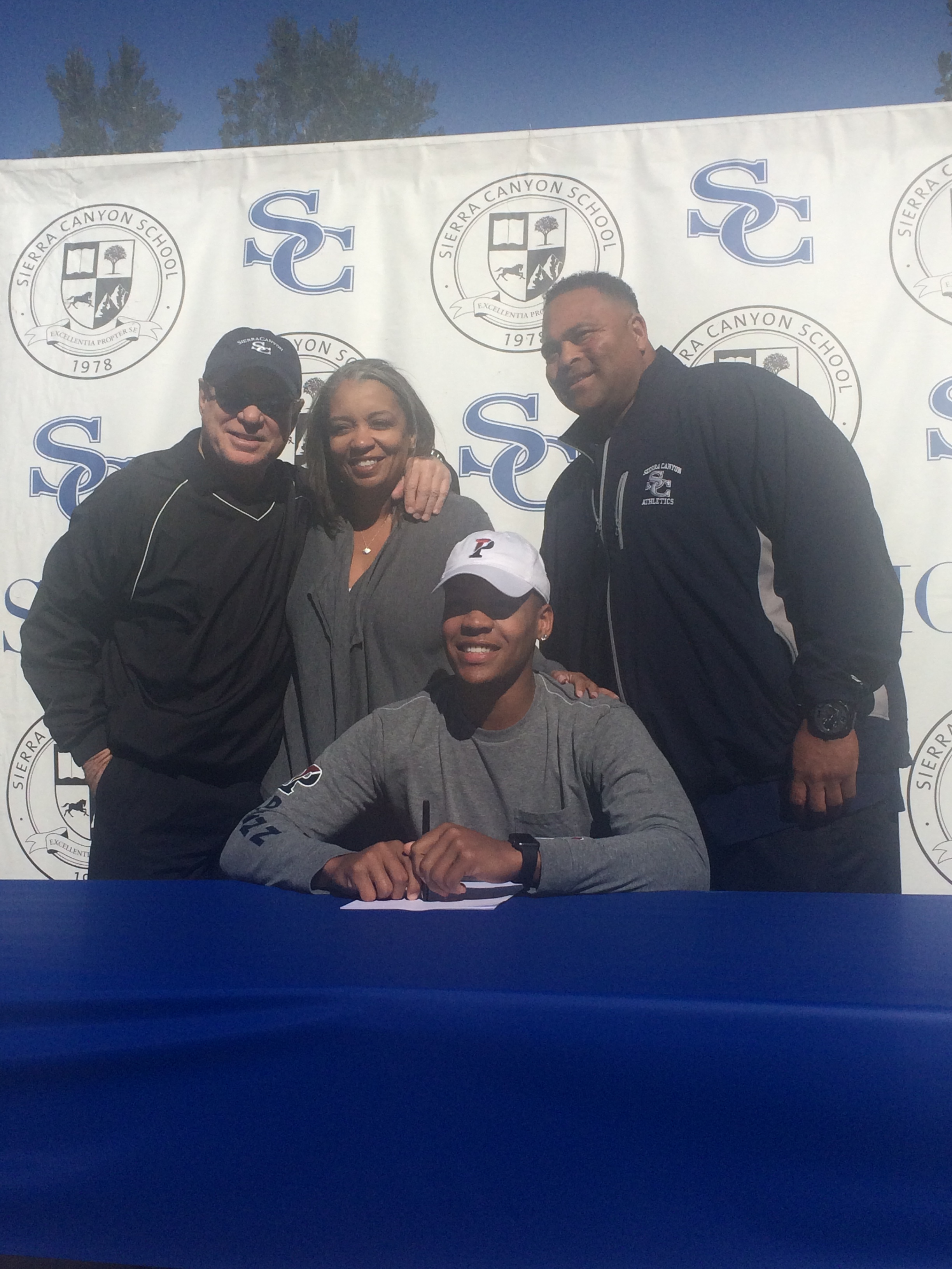 Kohl Hollinquest (Seated) poses for a picture with his mother (center), one of the two founders of Sierra Canyon, Howard Wang (Left), and Lower/Middle School Athletic Coordinator Steve Dasher (Right)