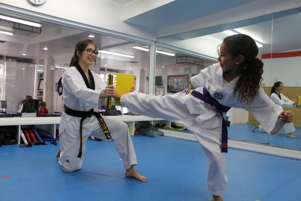 Taekwondo instructor Danielle Tolsma helps a student with board breaking.
