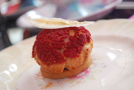 Red choux pastry with raspberry compote, green tea cream with a chocolate gold feather