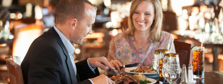 Man and woman eating food at restaurant