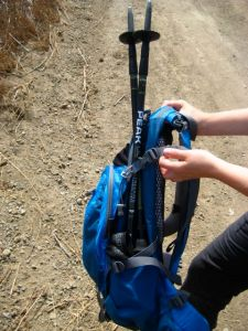 Trekking pole storage in a backpack that has side pockets and built in cinch straps