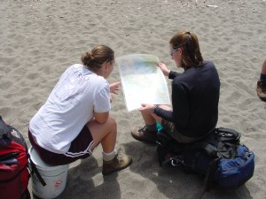 Two women sitting around a map on a sandy beach