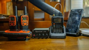 "My home ""shack"": a Yaesu VX-6R, SignalLink USB iPhone wireless charger, two Midland FRS radios, and a Garmin inReach Explorer. Not pictured are my iPad Pro and MacBook Pro."