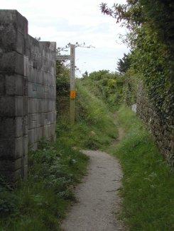 A footpath between stone and breeze-block walls