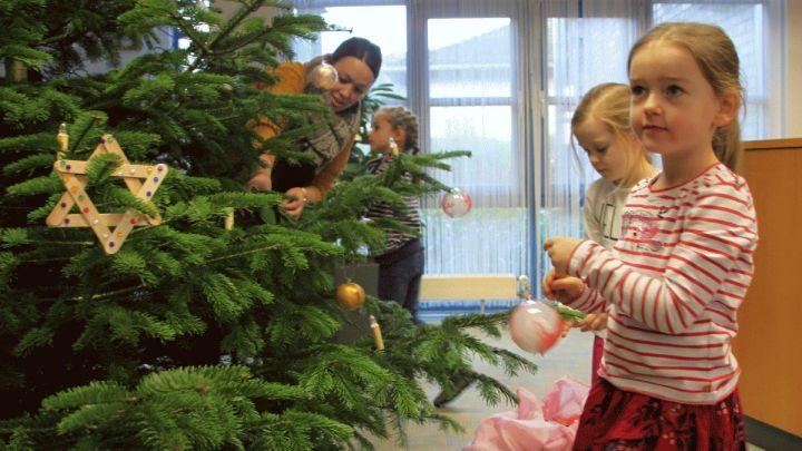 Kinder der Caritas-Kita Maria-Königin schmücken Baum in Giesener Sparkasse