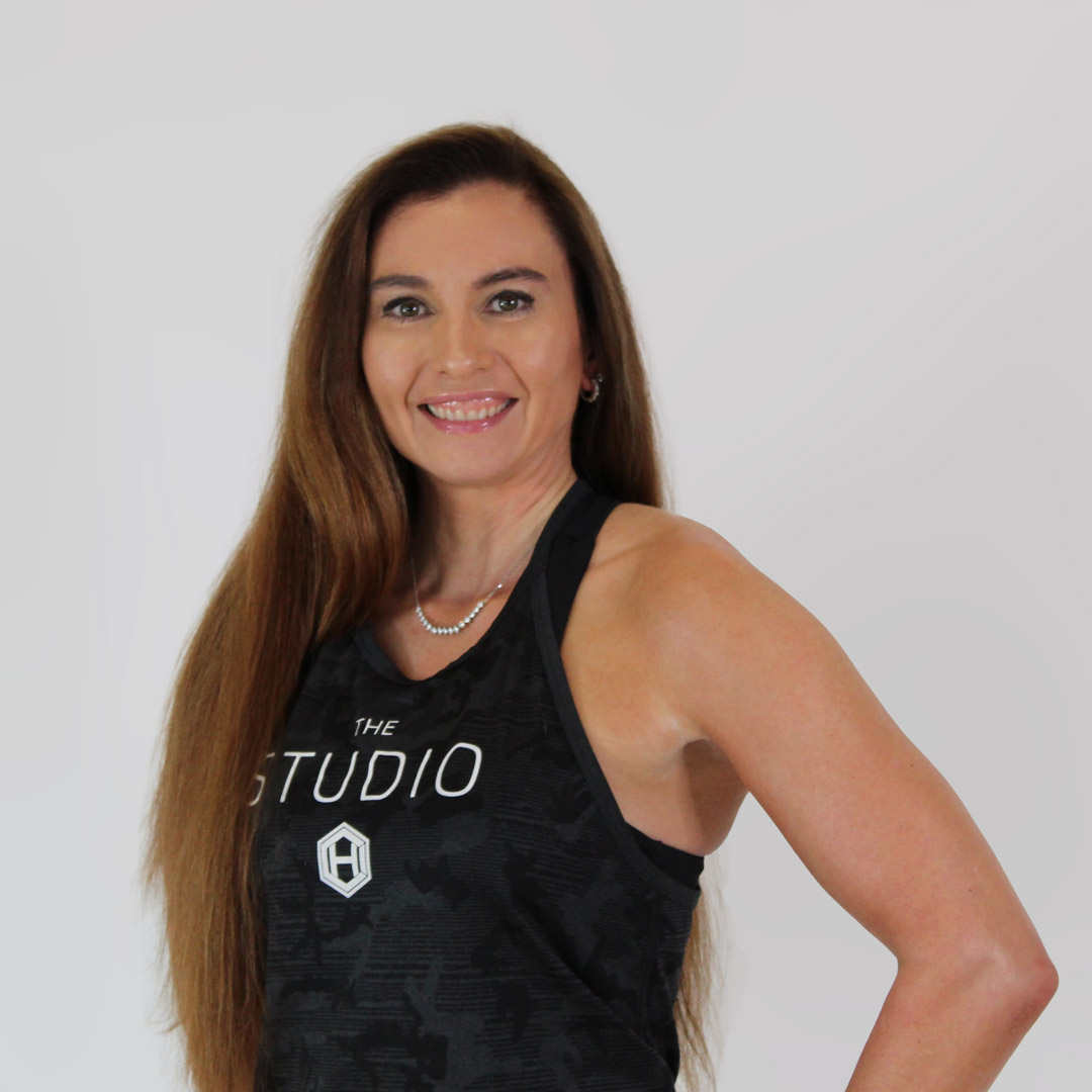 Brunette woman smiling with her right hand on her hip and wearing a black, hci studio tank top