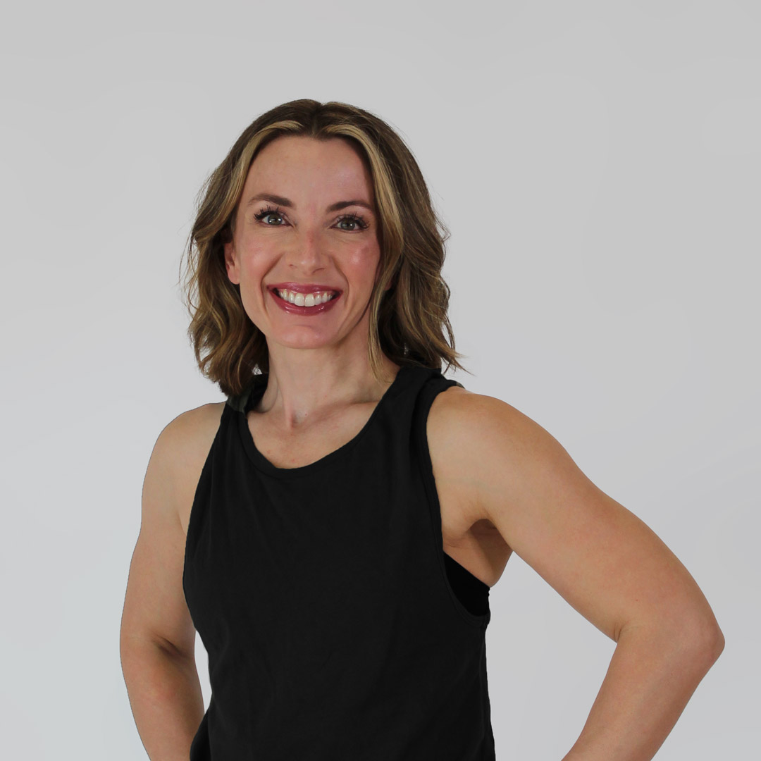 Woman wearing a black tank top and smiling with both her hands on her hips