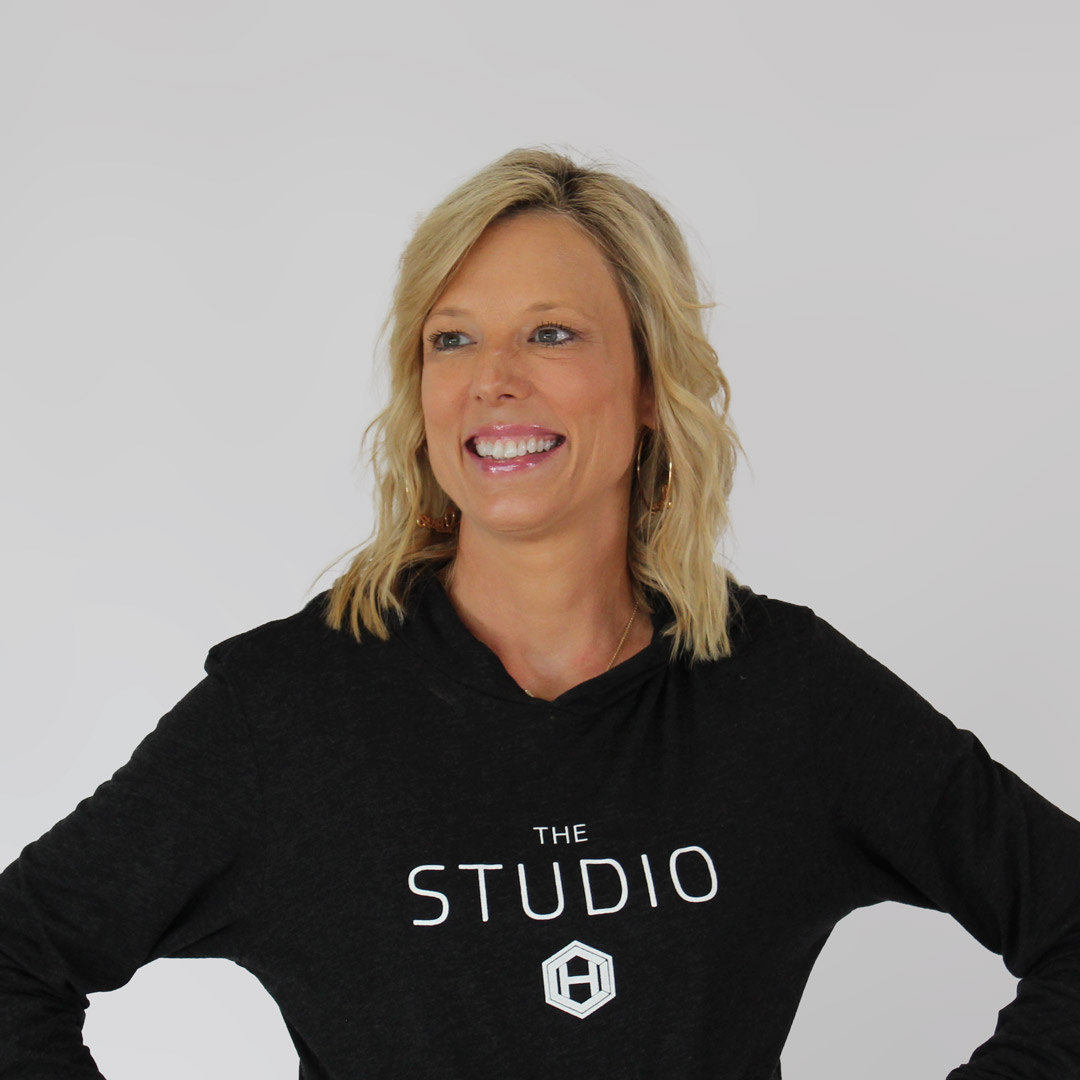 Blonde, blue-eyed woman smiling and looking to the left with her hands on her hips and wearing a black, hci studio hoodie