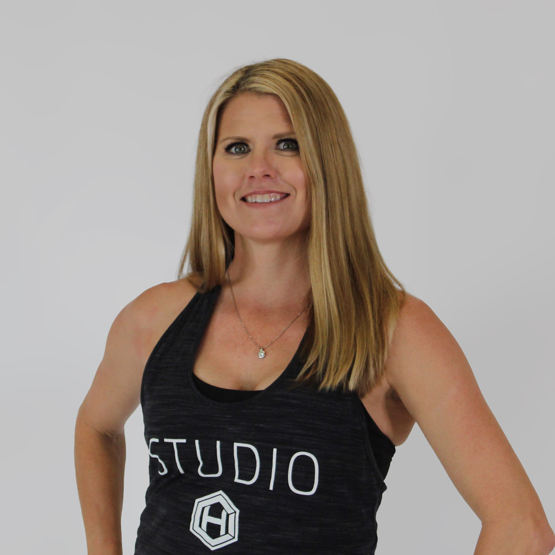 Blonde, blue-eyed woman smiling with hands on her hips wearing a black, HCI studio tank top
