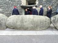 Exiting the Newgrange tomb, decorated kerbstone