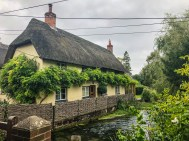 Thatched-roof home by stream in Wherwell, UK