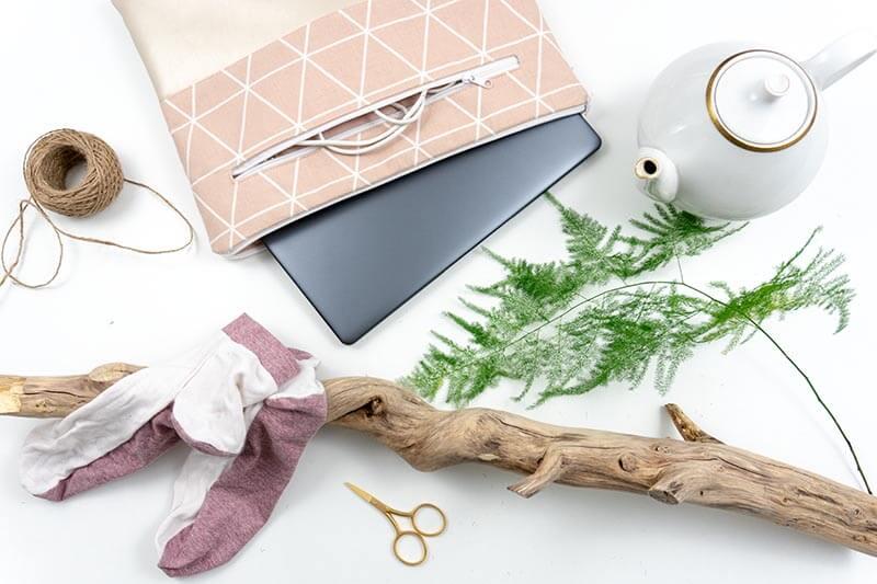 Flatlay mit Laptop, selbstgenähter Laptoptasche, selbstgenähten Socken, und Deko