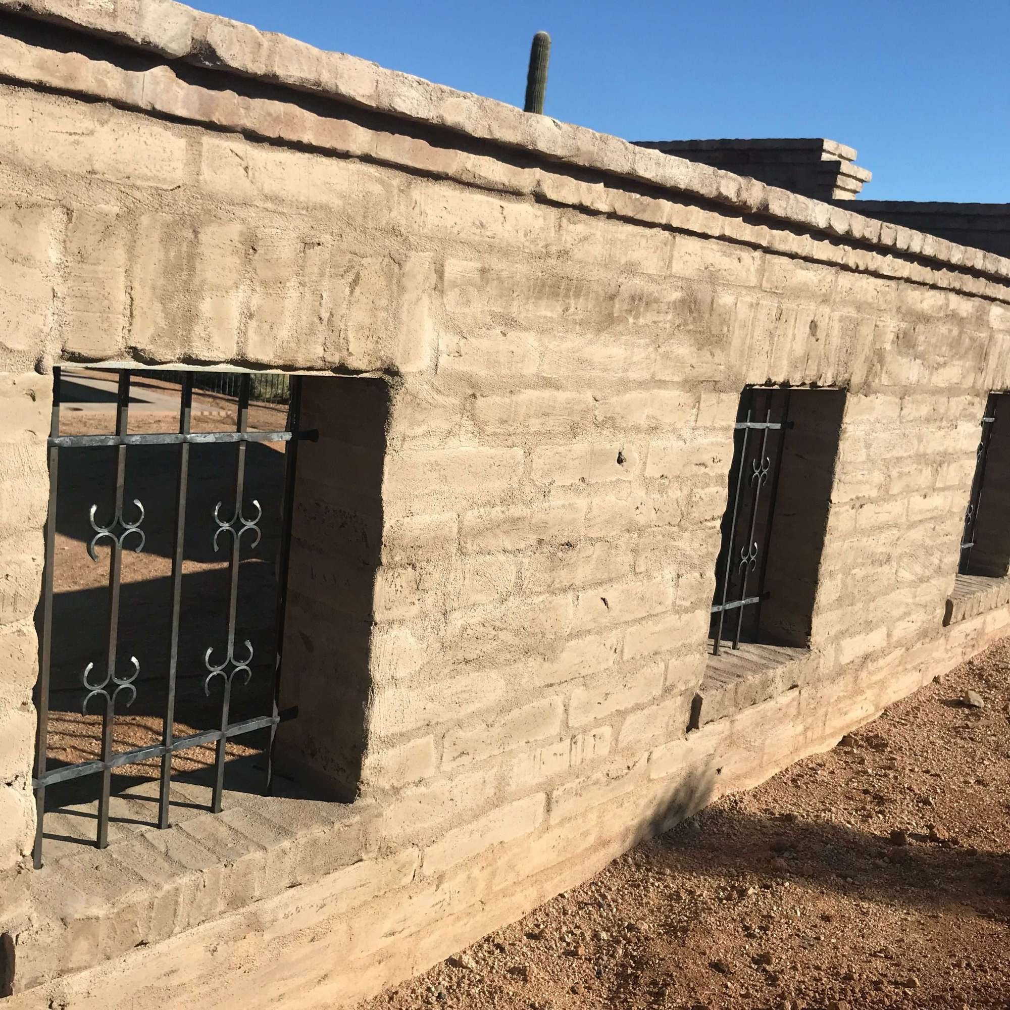 Adobe wall with wrought iron window grills