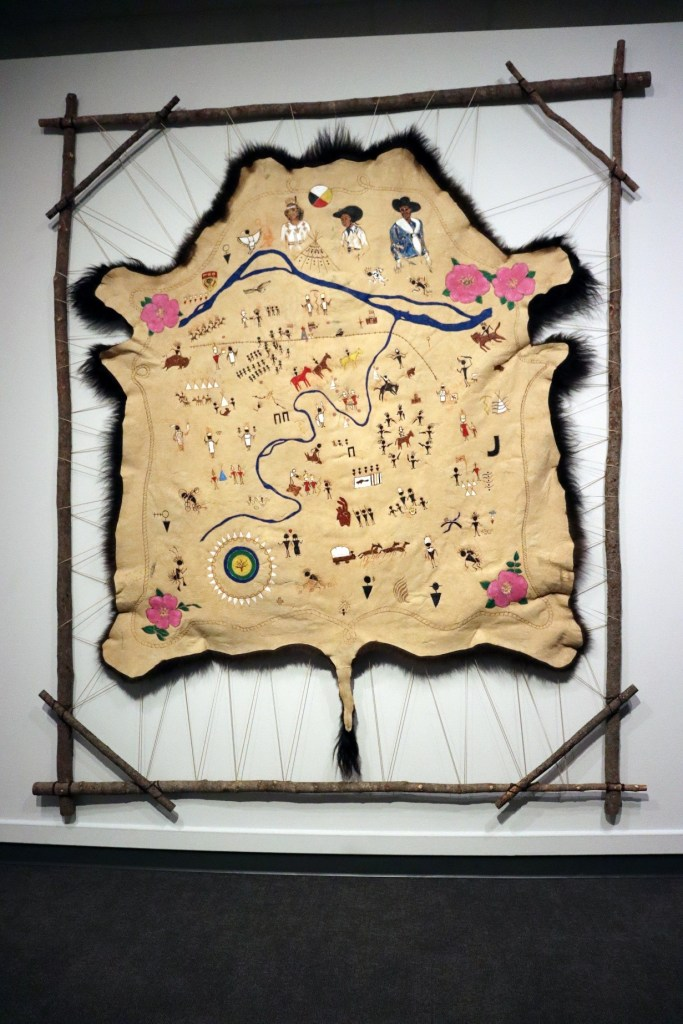The image depicts the map First Nations Stampede: A Guide to First Nations History at the Calgary Stampede by artist Adrian Stimson in a frame.