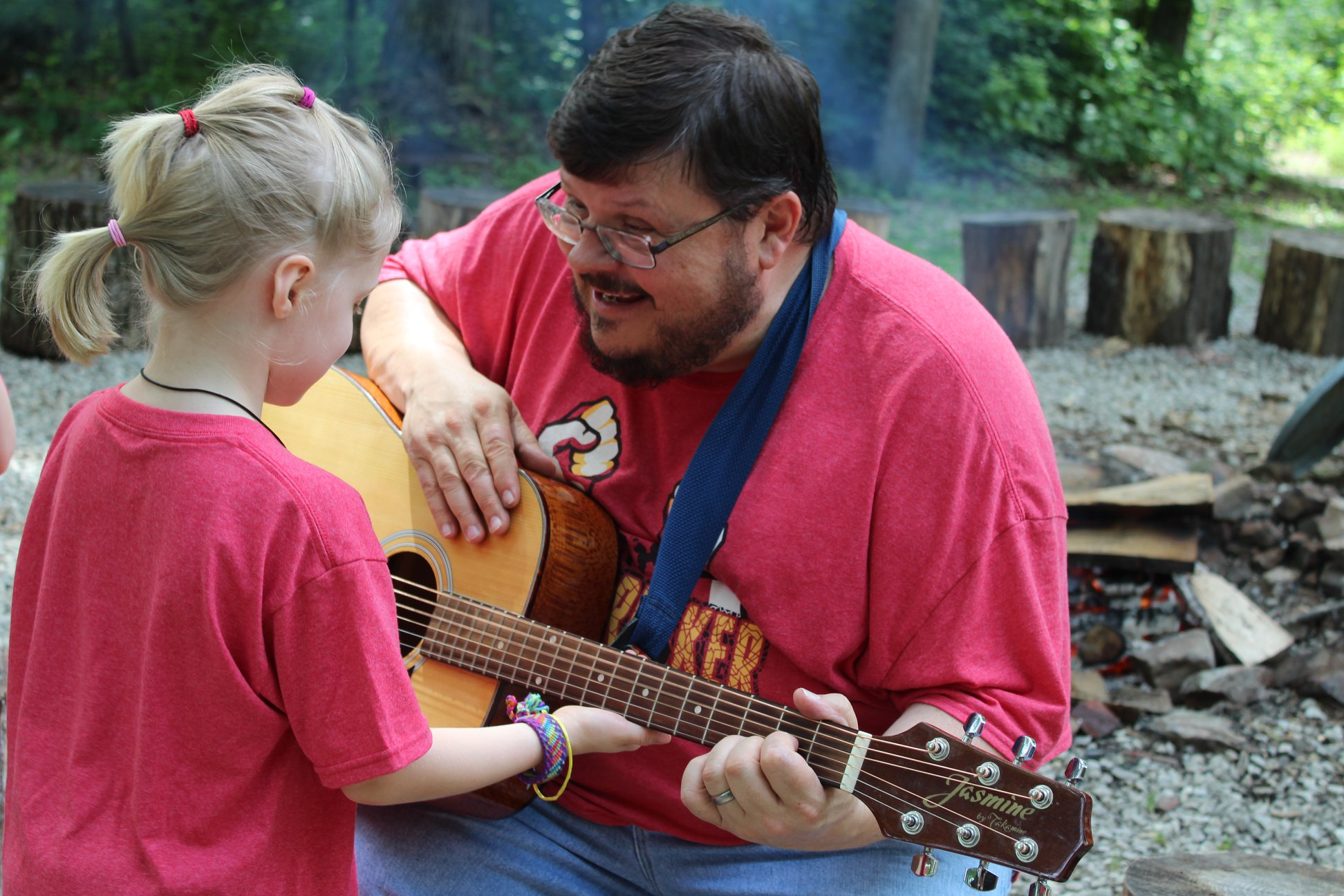 Counselor playing guitar with child at camp