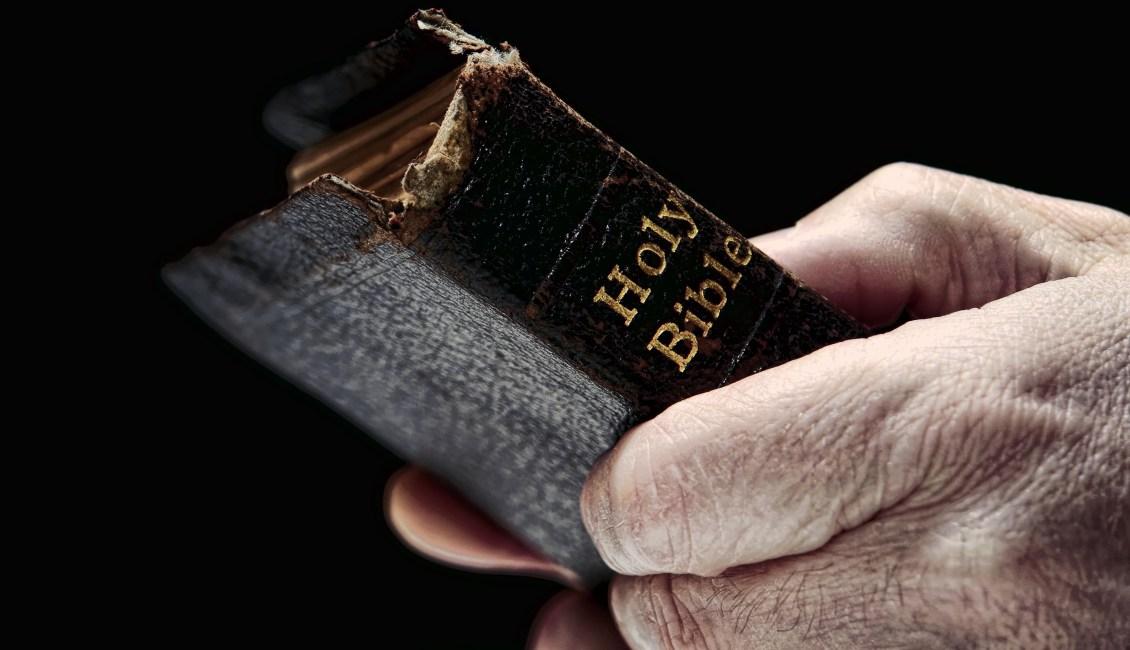 Man's hands holding Bible